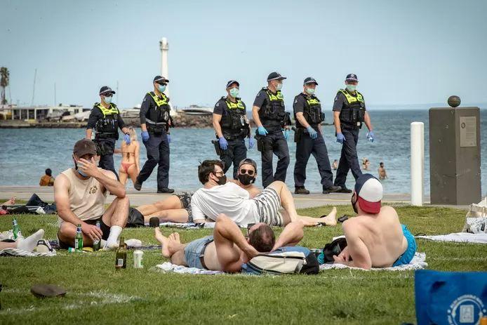 Policiers en patrouille en Australie, où de nombreuses personnes profitant du soleil portent le masque