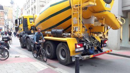Fietsers laveren tussen betonmixers