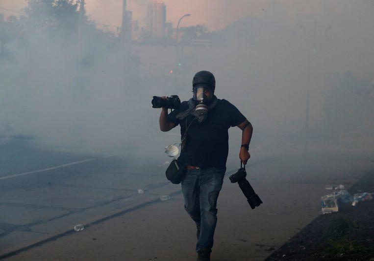 Een fotograaf rent door het traangas, bij de demonstraties in Minneapolis. Beeld Reuters