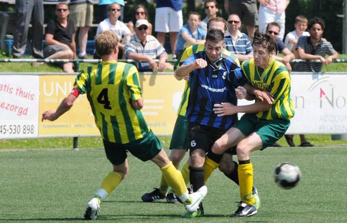 Karim el Ghoulbzouri (blauw/zwart shirt) probeert zich te ontworstelen aan drie spelers. Foto: William Hoogteyling