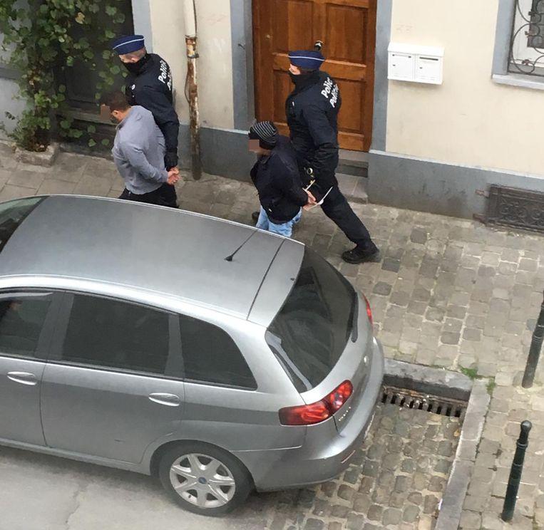 De politie leidt twee mannen weg nabij het huis van dader Issam T.