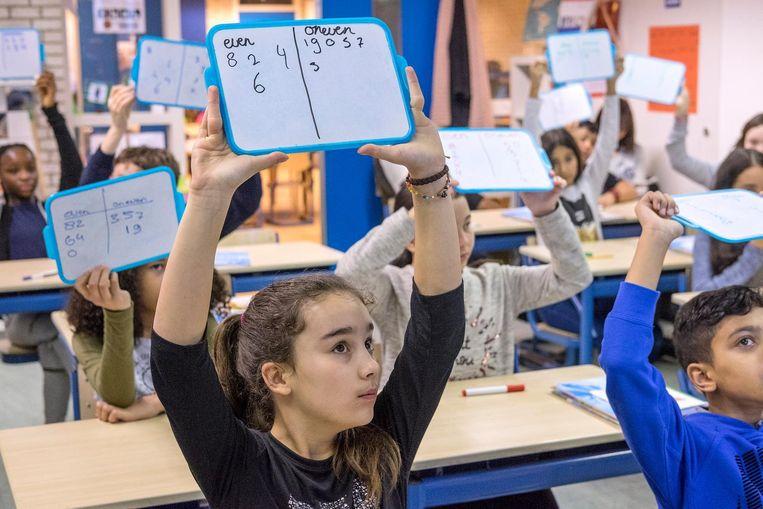 Tijdens de rekenles van juf Marie-José Glandorf op de Amsterdamse Alan Turingschool steken alle leerlingen bordjes op met het antwoord. Beeld Patrick Post