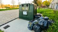 Berg vuilniszakken aan glascontainer