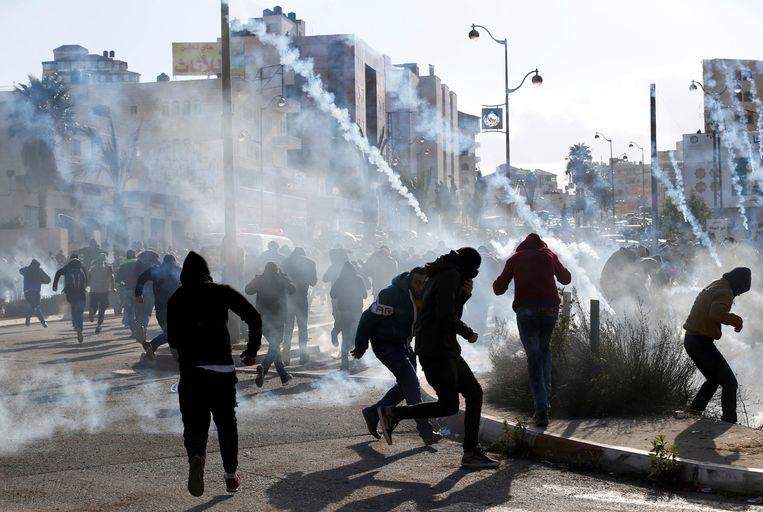 Palestijnse demonstranten rennen weg van het traangas dat de Israëlische troepen afvuren tijdens een protestactie tegen het besluit van Trump om Jeruzalem te erkennen als ISraëls hoofdstad.