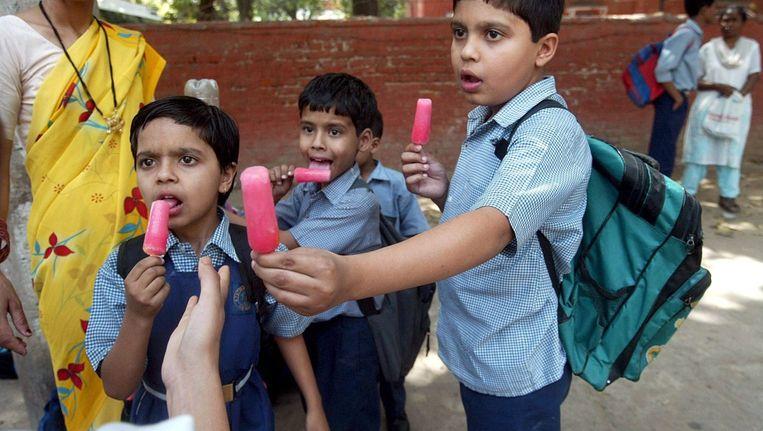 Indiase kinderen eten ijsjes op straat. Beeld anp