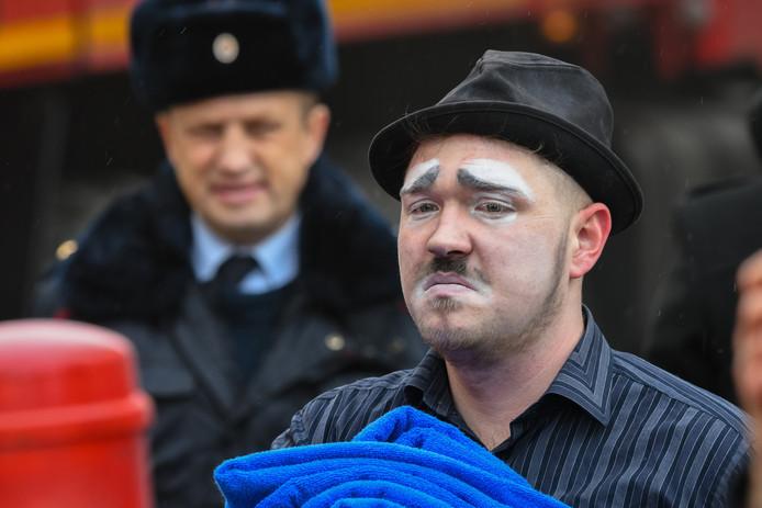 Een man die in de buurt aan het werk was als clown, staat met triest gezicht te kijken naar het brandende winkelcentrum Zimnaya Vishnya in de Russische stad Kemerovo. Ten minste 56 mensen zijn overleden, waaronder veel kinderen. Naar 60 mensen wordt nog gezocht. Foto Alexander Patrin