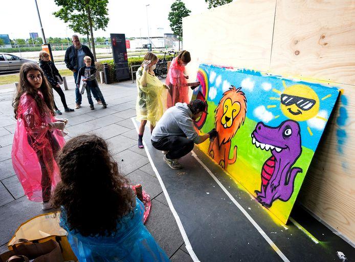 Utrecht - Samen met kinderen maakt een graffitikunstenaar bij The Wall een kleurrijk paneel voor het goede doel.