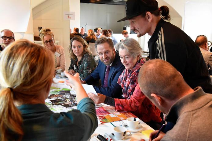Minister Hugo de Jonge (midden) in gesprek met bewoners en ondernemers. Staand met pet Johan Pijnacker.