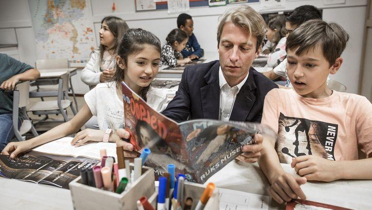 Taco Dibbits, directeur van het Rijksmuseum, deelt de eerste exemplaren uit aan groep 6 en 7 van openbare basisschool Rosa Boekdrukker Beeld Dingena Mol