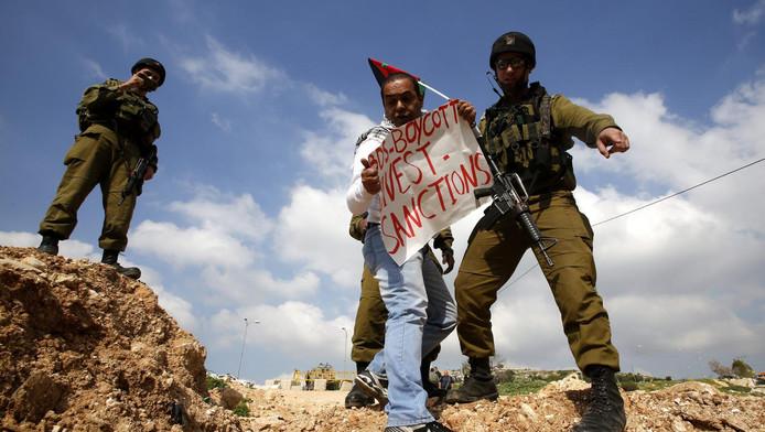 Israëlische militairen bij een demonstrant die een bord draagt met het opschrift BDS.