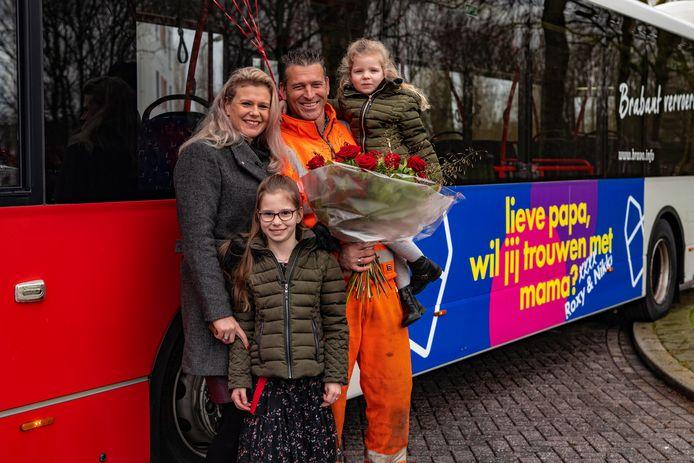 Rosemarie en Michel met hun dochters Nikky (op de arm) en Roxy naast de boodschap op de bus.