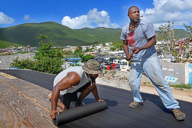 Dakdekkers zijn bezig op een door de orkaan zwaar getroffen huis. Een volledig herstel van Sint Maarten zal volgens de meeste schattingen zeker twee jaar duren. Beeld Guus Dubbelman / de Volkskrant