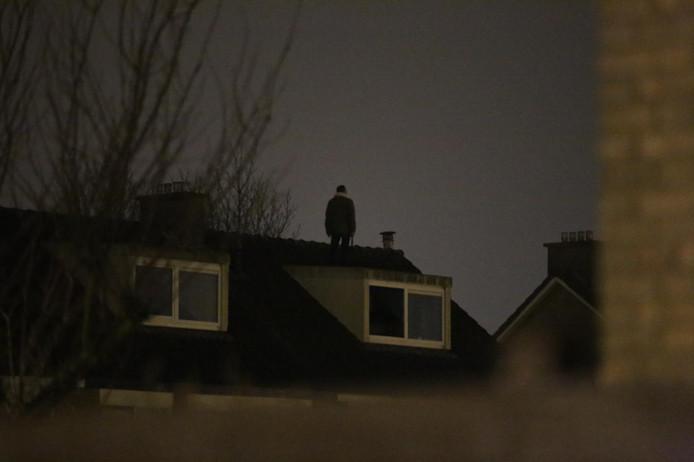 De man met de bijl op het dak van een woning aan het Oudeschanspad in Arnhem-Zuid.