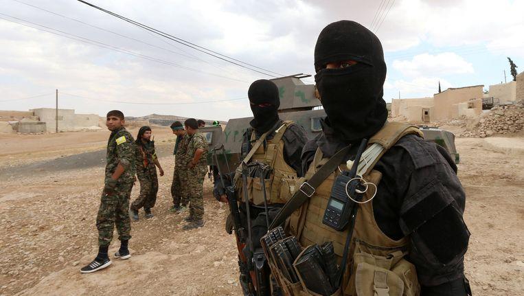 Strijders van de SDF hebben zich verzameld in de buitenwijken van Manbij. Beeld reuters