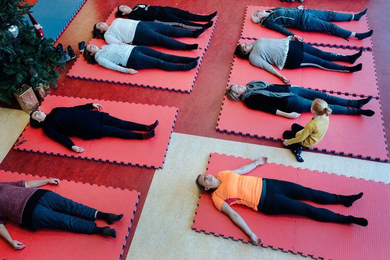 Leraren van basisschool De Meent in Waalre nemen deel aan een workshop yoga, als onderdeel van de landelijke stakingsdag in het basisonderwijs. Beeld Merlin Daleman
