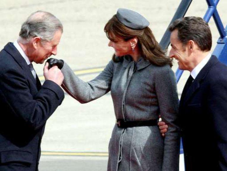 Prins Charles heet de Sarkozy's van harte welkom op Heathrow.