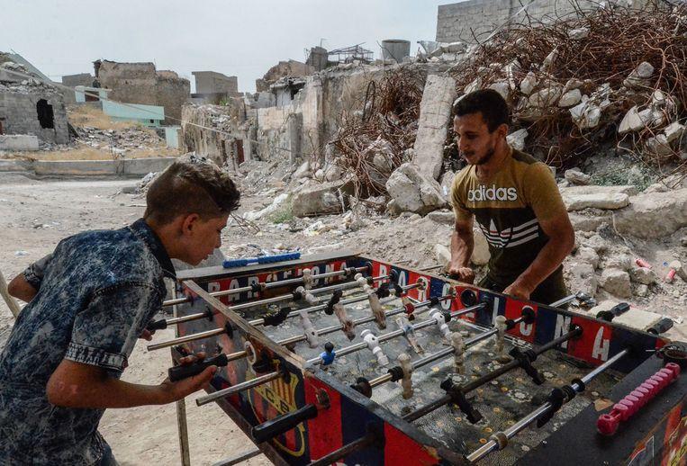 Twee inwoners van Mosul spelen een potje tafelvoetbal. Ook in de tweede stad van Irak, die nog grotendeels in puin ligt door  gevechten met IS, is afgelopen dagen Suikerfeest gevierd. Beeld AFP