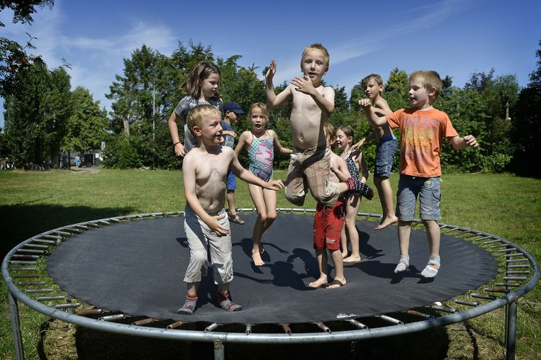 De kinderen amuseren zich op de trampoline.