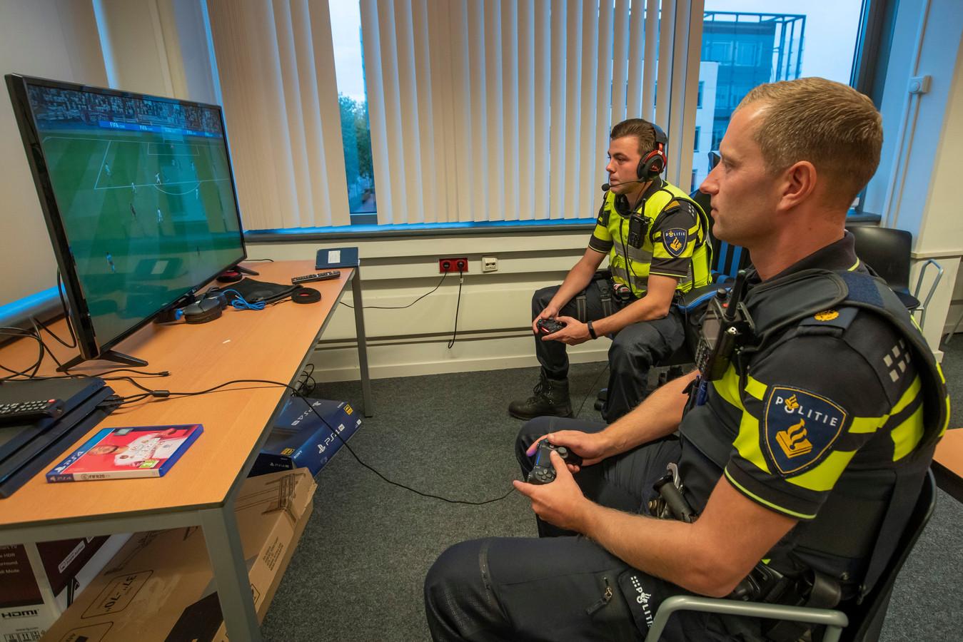 Politieagenten Juliën Nijsen (l) en Arthur van der Heijden hebben al gamend contact met jongeren.