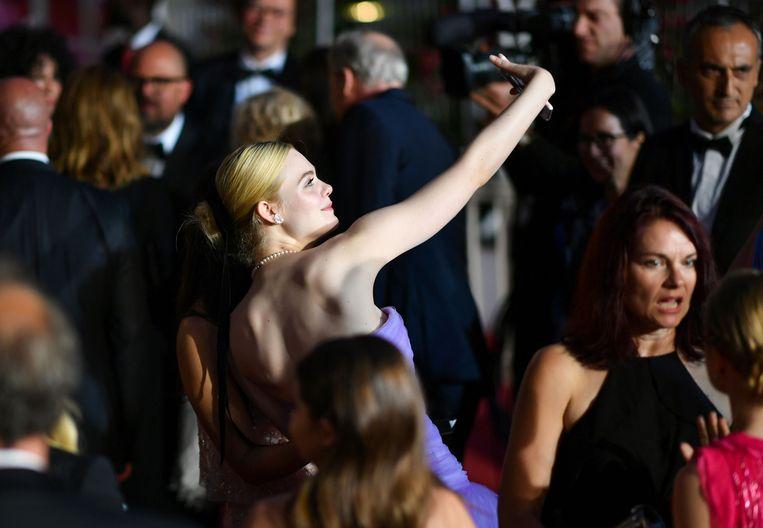 Actrice Elle Fanning maakt een selfie op de rode loper in Cannes. Beeld AFP