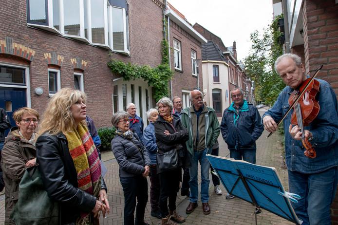 Violist Jan-Willem Vis vergast de bezoekers voor zijn woning in de Langestraat op een mini-concertje.