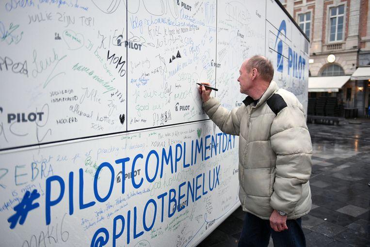 Een passant schrijft een complimetnje op de zijkant van de bus.