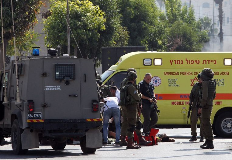 Israëlische soldaten en hulpdiensten verzorgen een militair die vrijdagmiddag neergestoken werd door een Palestijn die zich voordeed als journalist. De aanvaller werd doodgeschoten. Beeld afp