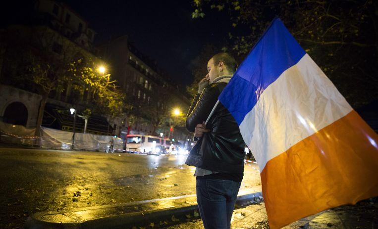 Een man met een Franse vlag kijkt naar Cafe Bataclan, daags na de aanslagen in Parijs. Beeld anp