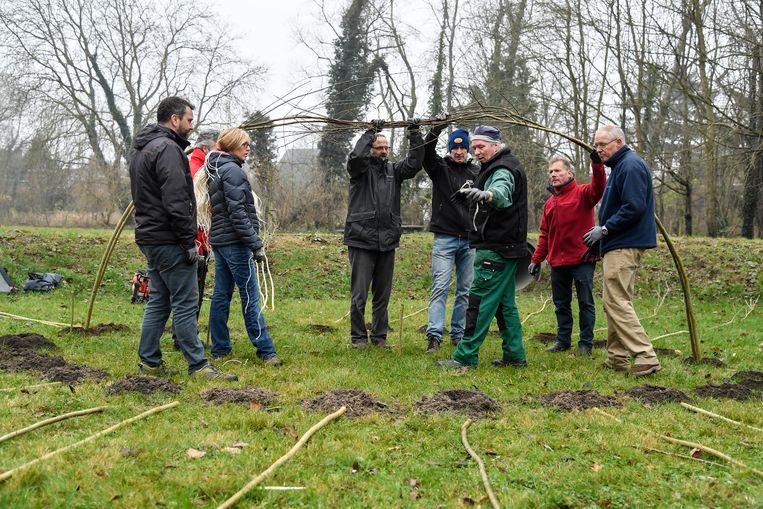 De vrijwilligers leren hoe ze met wilgentakken een hut moeten bouwen.