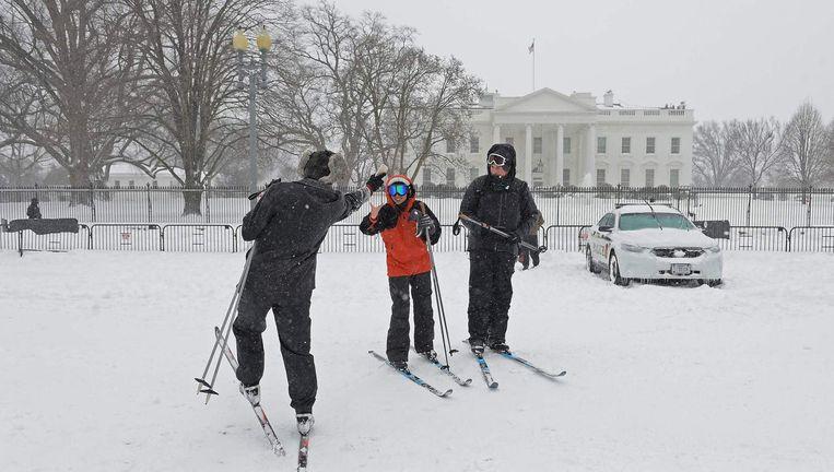 Inwoners van Washington pauzeren bij het Witte Huis tijdens het langlaufen. Beeld AFP