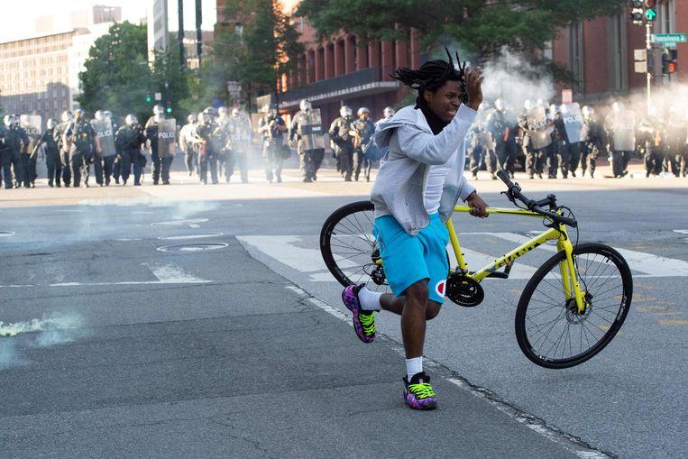 Een demonstrant ontvlucht de politie, die traangas en rubberen kogels gebruikt om demonstranten bij het Witte Huis uit elkaar te drijven. Beeld AFP