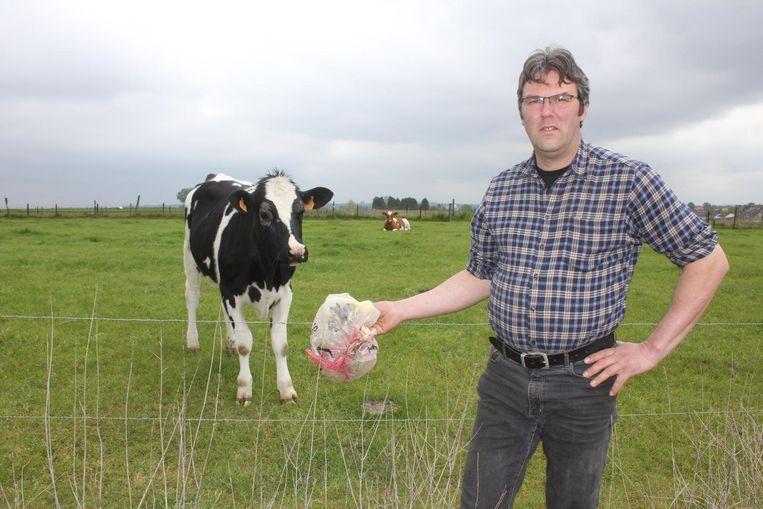 Landbouwer Stefan Buydens met een gedumpte zak afval aan de weide van zijn koeien.