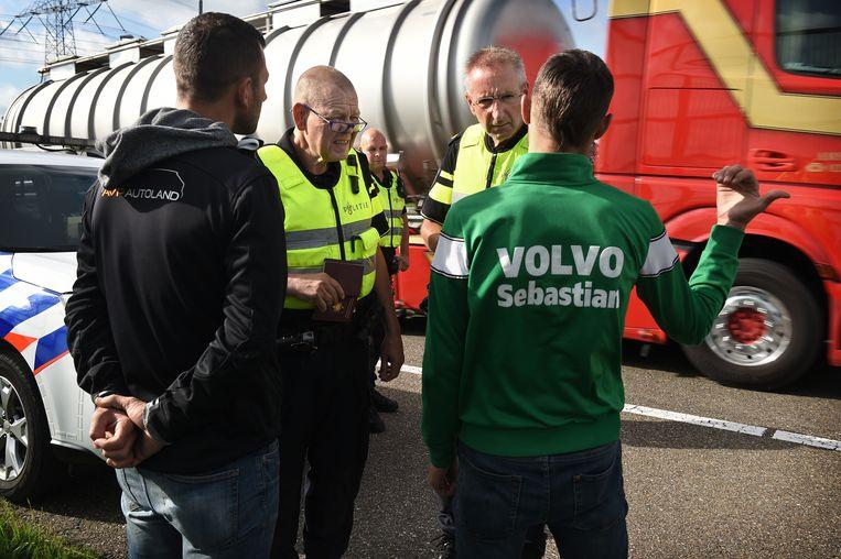 De politie houdt twee Albanezen aan die langs de snelweg lopen.  Beeld Marcel van den Bergh