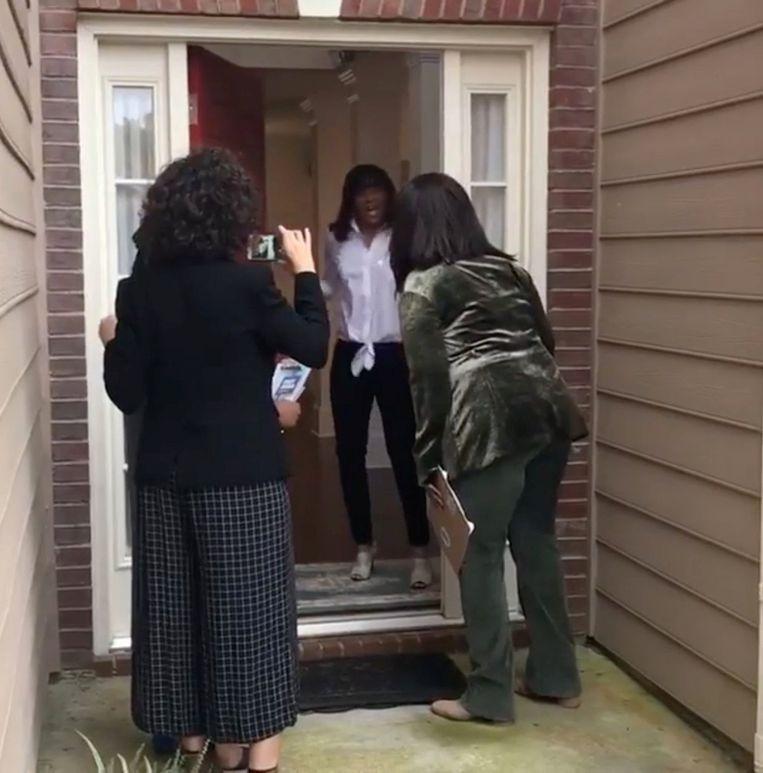 Een inwoner van Georgia is stomverbaasd als zij donderdag de deur opendoet en oog in oog staat met Oprah Winfrey. De miljardair voerde donderdag campagne voor gouverneurskandidaat  Stacey Abrams.  Beeld REUTERS