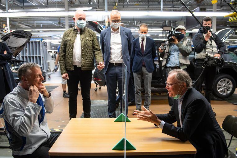 De premier van Nedersaksen (rechts) in gesprek met de manager van de Volkswagen-fabriek in Wolfsburg. Staand onder andere OR-voorzitter Bernd Osterloh (links) en topman Herbert Diess (rechts, met stropdas). Beeld Getty Images