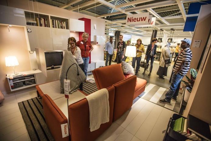 Femke Baten (links) en Ellen Hendrix van IKEA laten zien hoe een bank wordt omgetoverd in een bed. Foto Ton van de Meulenhof