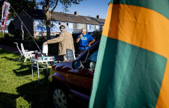 Een deelnemer aan de 'Alternatieve Vierdaagse' krijgt langs de weg in Elst een kop koffie.