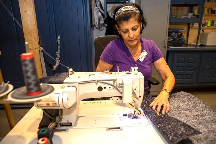 Medewerkerster Samira Noja maakt in het naaiatelier van Het Goed in Best tassen van vilt. Deze sterke stof is gemaakt van de weggegooide kleding die bij Het Goed in Schijndel hiervoor gesorteerd is.