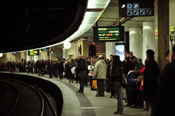 Mensen wachten in Brussel Centraal op een vertraagde trein.