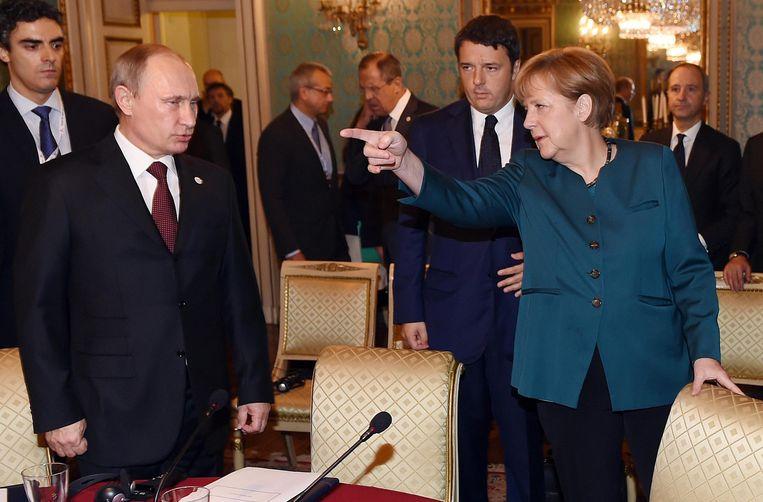 De Duitse Bondskanselier Angela Merkel (R) en Vladimir Poetin bij een internationale top in oktober. Beeld ap