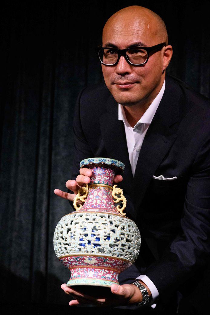 Nicolas Chow van Sotheby's Asia poseert trots met de vaas tijdens een mediabijeenkomst eind juni in Hongkong.