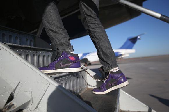 Een migrant wordt vanuit Mesa in Arizona geboeid het vliegtuig naar Honduras opgestuurd. Foto uit 2013.