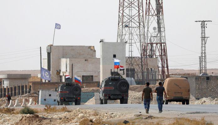 Russische en Syrische vlaggen op militaire voertuigen bij de stad Manbij.