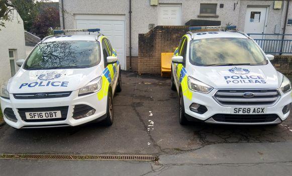Twee Schotse politiewagens, met rechts het woord 'politie' ook in het Schots-Gaelisch.