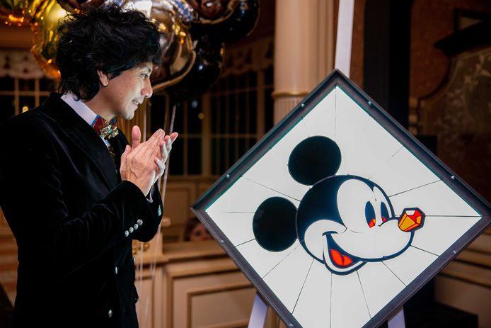 Wibi Soerjadi viert zijn 50e verjaardag in Disneyland Paris. Hij kijkt naar het kunstwerk dat hij kreeg van Zwolse kunstenaar Arjan Boeve.