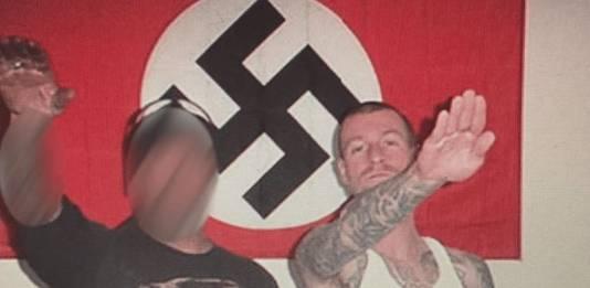 Michael brengt de Hitlergroet.  Hij maakte deel uit van een gewelddadige skinheadgroep.