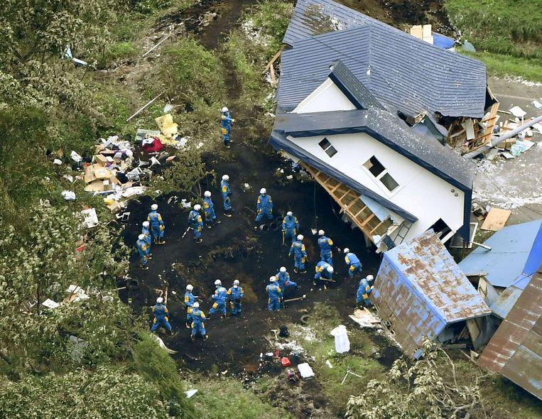 De politie zoekt naar overlevenden bij een huis dat zwaar beschadigd en verplaatst is door de aardbeving.