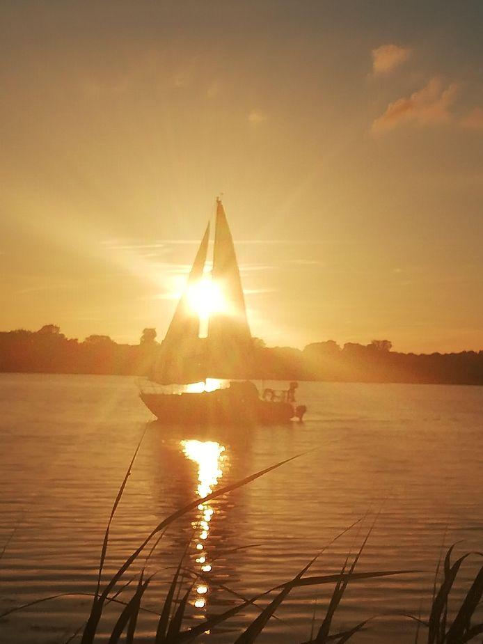 Genieten van een mooie zomeravond op een terras aan de Kralingse plas. Een zeilbootje glijdt zachtjes voorbij.