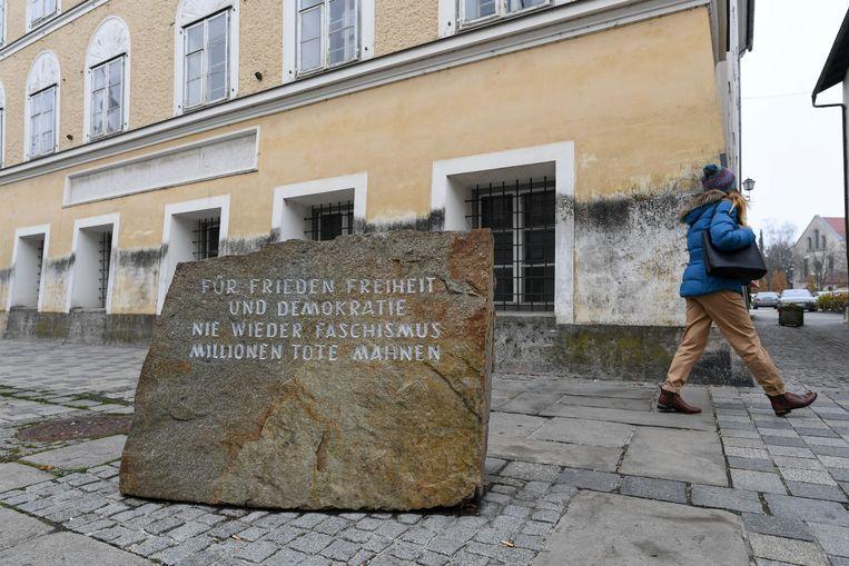 Het geboortehuis van Hitler in Braunau, waarvoor een gedenksteen werd geplaatst met onder meer de woorden 'nooit meer fascisme'. Beeld Reuters
