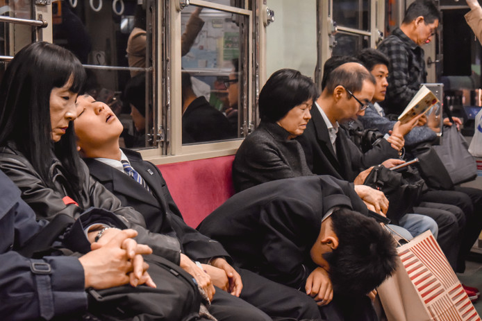 Japanse werknemers in Hiroshima doen een dutje in het openbaar vervoer.